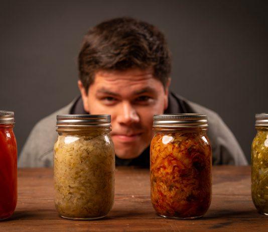 Muž, ktorý sa pozerá na poháre s fermentovanou zeleninou.