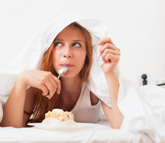 žena, ktorá leží na posteli a konzumuje koláč
